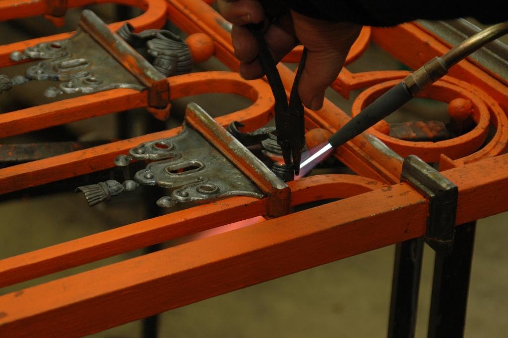 Letzte Richtarbeiten an den neu gefertigten Zierelementen; Gitter gereinigt und mit Bleimennige konserviert